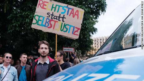 """An anti-Nazi protester holds a sign reading, """"Rule of law instead of vigilante justice"""" in Chemnitz on Monday."""