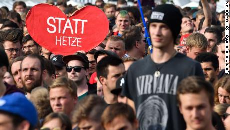 """A crowd member holds a sign reading """"Instead of hate"""" at the concert in Chemnitz."""
