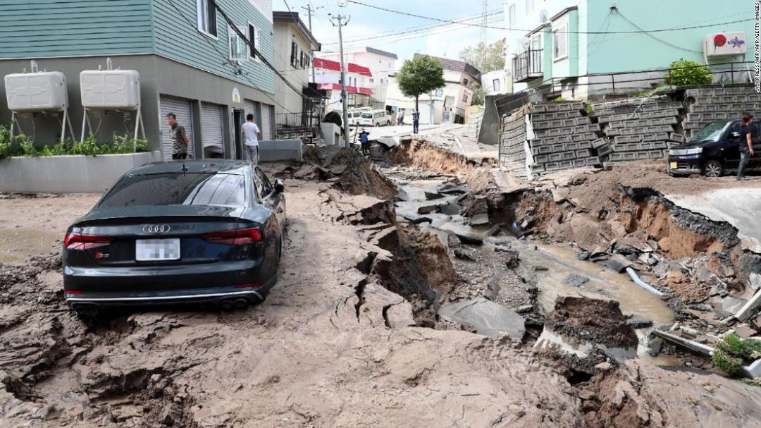 A car is seen stuck on a road damaged by an earthquake in Sapporo, Hokkaido prefecture on September 6, 2018.