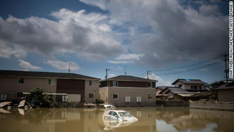 A car sits in water after the area was devastated by flooding and landslides in Mabi, Okayama prefecture on July 10, 2018.