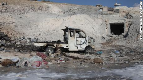 A burned vehicle and personal belongings are seen Saturday in Hass, Syria, after an airstrike.