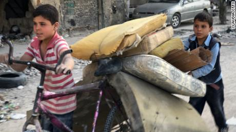 Boys in the city of Douma transporting mattresses for their families. Many of the locals have rolled up their sleeves to refurbish their homes, receiving little support from the cash-strapped government. After a brutal siege and government offensive forced out the rebels that controlled Douma, the city is in tatters.