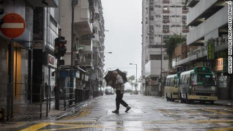 A man uses his umbrella while crossing a road as  Mangkhut edges closer to Hong Kong Sunday