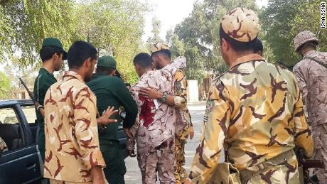 A soldier injured in the attack is treated at the scene in the southern Iranian city of Ahvaz.