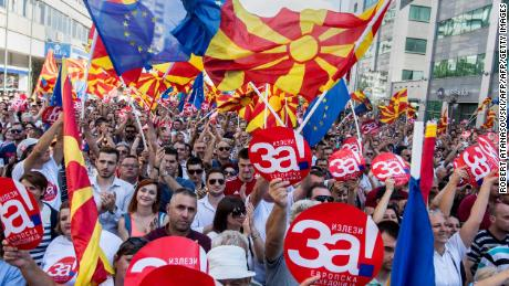 "People wave Macedonian and European flags as they attend a rally for the ""yes"" campaign."