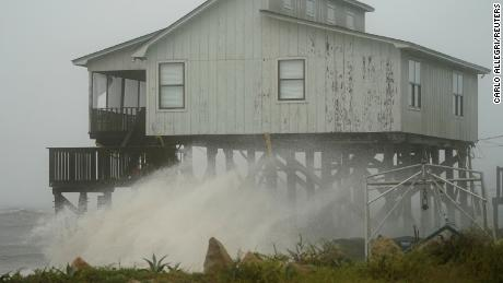 Waves sweep over a house as the storm comes ashore Wednesday in Alligator Point.
