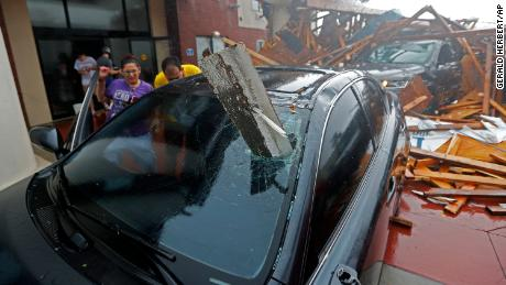 A woman checks on her vehicle after the hotel canopy collapsed in Panama City Beach.