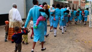 Young women dressed in uniform walk their children to daycare before attending trades courses at the Faraja Center, a shelter for vulnerable women.