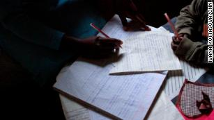 Elifuraha's son watches, pencil in hand, as she flips through her notes from a tailoring class at the Faraja Center.