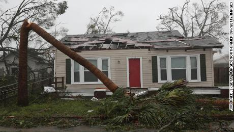 Michael pokes holes in the roof of a Panama City home and snaps a palm tree Wednesday.