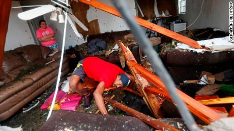 Dorian Carter searches for his missing cat after several trees fell on his Panama City home Wednesday.