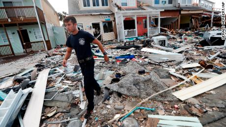 A firefighter searches door to door after Hurricane Michael in Mexico Beach.