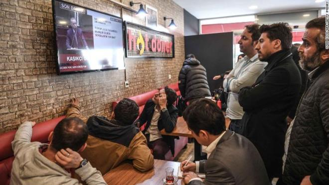 People gather around a TV at an Istanbul cafe to watch Erdogan's speech.