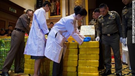 Thai national police chief general Chaktip Chaijinda (second from the right) watches police department chemists inspect seized drugs during a press conference in Bangkok on May 11. Ten million yaba pills made in Myanmar and nearly half a tonne of crystal meth hidden in tea packages was  seized from a convoy in downtown Bangkok, Thai police said.