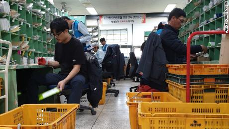 Workers for Korea Post sort packages and letters. The company has faced repeated pressure from workers and the government to reduce employee hours on the job.