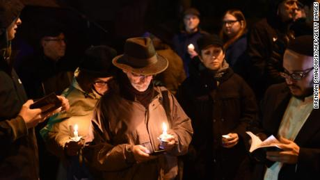 People hold candles outside the Tree of Life Synagogue after a shooting there left 11 people dead in the Squirrel Hill neighborhood of Pittsburgh on October 27, 2018.