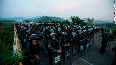 A wall of police in riot gear blocked a highway to stop thousands of migrants in the Mexican state of Chiapas on Saturday.