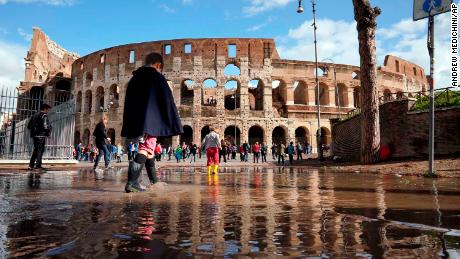 Children play in a puddle by the ancient Colosseum in Rome on Tuesday, a day after strong winds and rain hit the city.