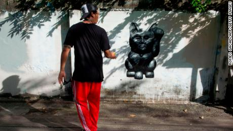 """The Thai street artist who goes by the name of """"Headache Stencil"""" walks next to his graffiti caricature of Thailand's junta chief depicted as a """"lucky cat"""" with paw raised to rake in money, spray-painted on a fence in Bangkok."""