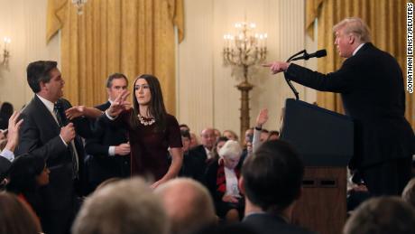 A White House staff member reaches for the microphone held by Jim Acosta as he questions Trump.