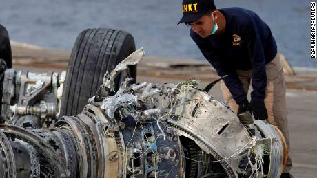 An Indonesian National Transportation Safety Commission (KNKT) official examines a turbine engine from the Lion Air crash.