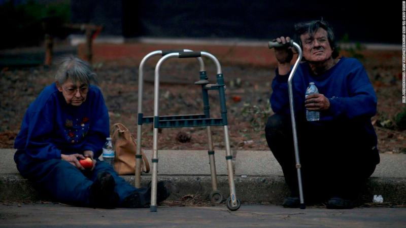 Juanita and Wayne McLish sit on a curb November 8 after losing their house to the Camp Fire in Paradise.