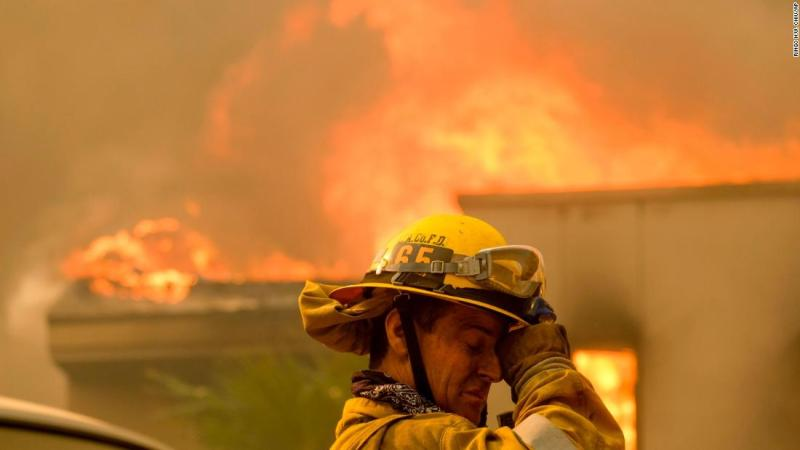 A firefighter keeps watch as the Woolsey Fire burns a home near Malibou Lake on Friday.