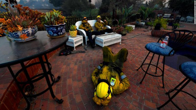 From left, firefighters Cory Darrigo, Omar Velasquez and Sam Quan rest in a Westlake Village backyard after battling the Woolsey Fire all night.