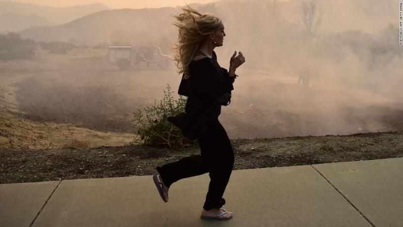 A woman runs in Calabasas as firefighters work to control a flare-up from the Woolsey Fire on Saturday, November 10.