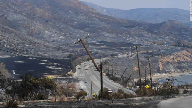 Scorched hillsides and damaged power lines are seen along the Pacific Coast Highway in Malibu on November 10.