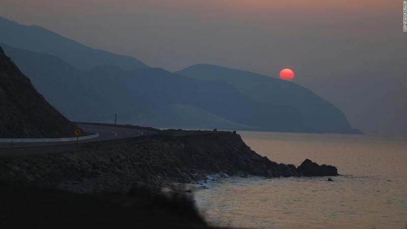 The sun rises over the Pacific Ocean as the Woolsey Fire burns in Malibu on November 11.