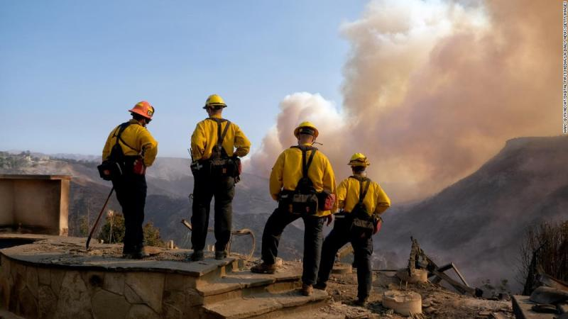 Culver City firefighters watch the Woolsey Fire from a burned home in Los Angeles on November 11.