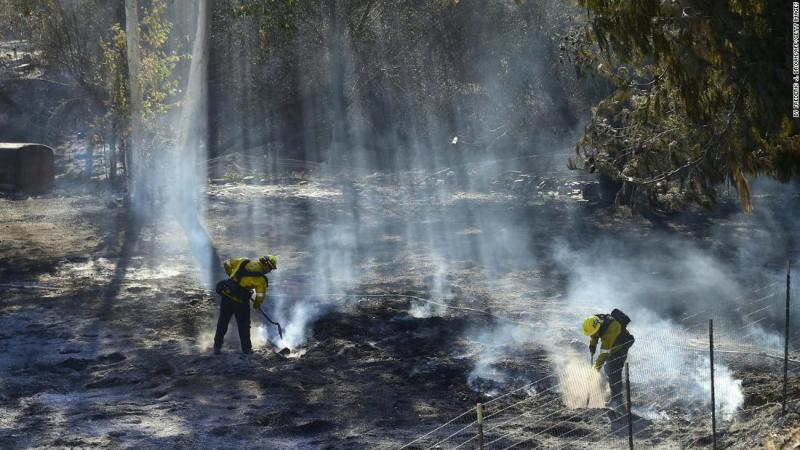 Firefighters douse embers off a canyon road that cuts across the mountains to Malibu.