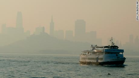A ferry boat makes its way toward Alcatraz Island as the San Francisco skyline in is obscured by wildfire smoke and haze.