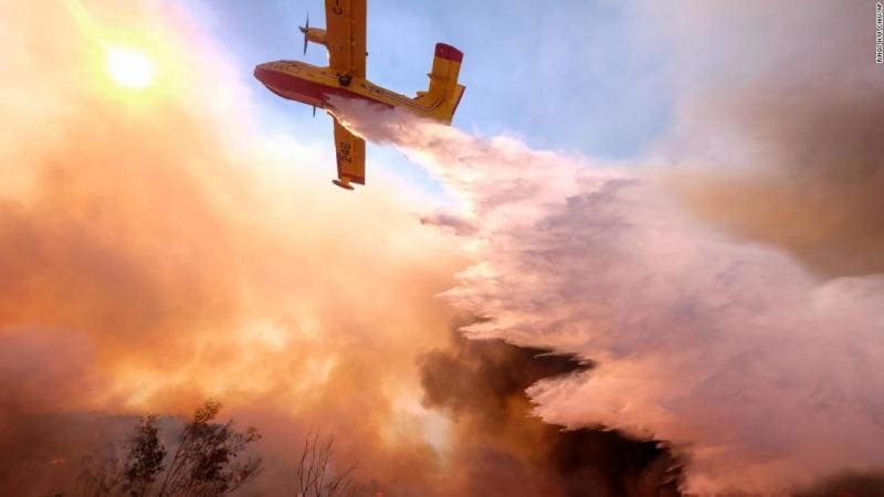 An air tanker drops water on a fire on Monday, November 12, along the Ronald Reagan Freeway in Simi Valley, California.