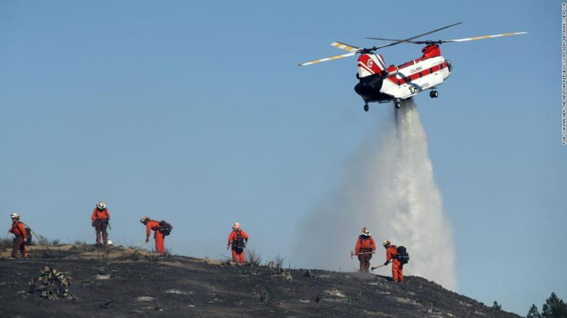 Firefighters put out hot spots on November 12 as the Hill Fire burns in a canyon in Thousand Oaks, California.