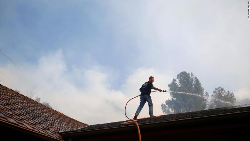 A resident sprays down a roof on November 12 as firefighters battle the Peak Fire in Simi Valley.
