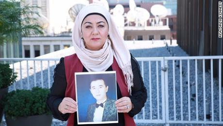 Uyghur journalist Gulchehra Hoja holds a pictures of her brother who has been missing in Xinjiang for more than a year