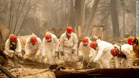 Rescue workers sift through rubble in search of human remains in Paradise.