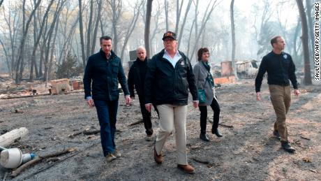 US President Donald Trump (C) walks with Paradise Mayor Jody Jones (2R), Governor of California Jerry Brown (2L), Administrator of the Federal Emergency Management Agency, Brock Long (R), and Lieutenant Governor of California, Gavin Newson, as they view damage from wildfires in Paradise, California on November 17, 2018. - President Donald Trump arrived in California to meet with officials, victims and the