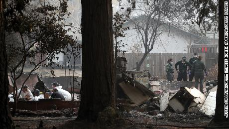 Sheriff deputies and rescue workers recover human remains from a home destroyed by the Camp Fire.