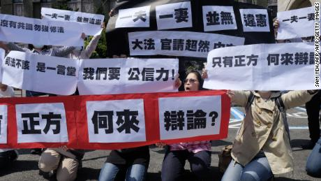 """Conservative activists display signs reading """"one husband, one wife does not go against the constitution"""" in Taipei, on March 24, 2017."""