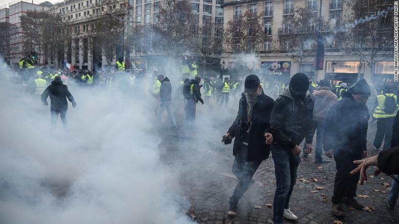 Protesters clash with riot police who fired  tear gas canisters in central Paris on Saturday.