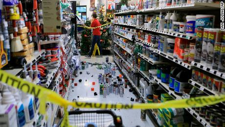 An employee walks past a damaged aisle at an Anchorage True Value hardware store.