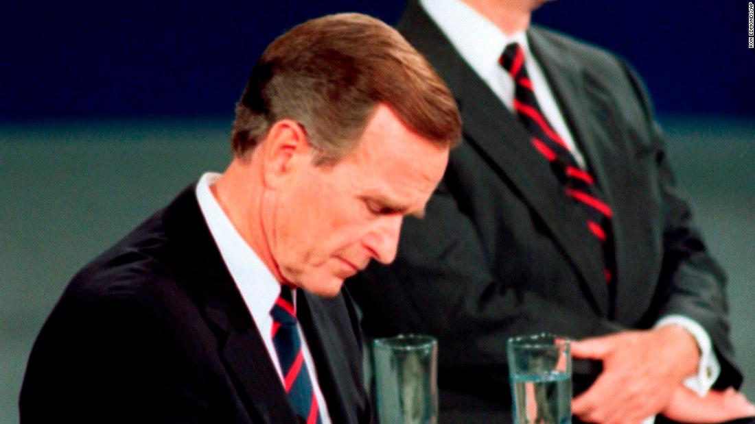Bush checks his watch during a 1992 presidential debate with Ross Perot, right, and Bill Clinton. The memorable moment was interpreted as the President being out of touch.