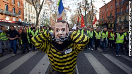 "Demonstrators with the ""gilets jaunes"" or ""yellow vest"" movement call for the French President Emmanuel Macron to resign at a demonstration last month."