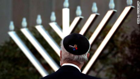 Rabbi Jeffrey Myers watches the installation of a menorah outside the Tree of Life Synagogue before a Hanukkah ceremony Sunday evening.
