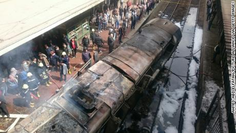 Rescue workers stand next to burned-out wagons sitting on railway tracks Wednesday in Cairo.