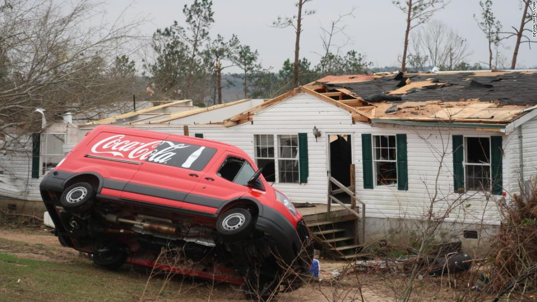 A van is upended in front of a damaged home in Lee County.
