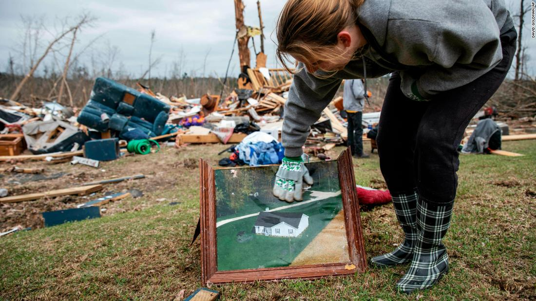 Ashley Griggs wipes away dirt from a photo that shows what a Beauregard home looked like before it was destroyed.